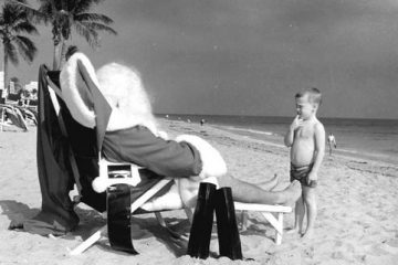 Child looking at Santa on the beach