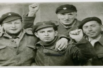 Ritratto di gruppo: quattro volontari combattenti di età diverse salutano col pugno chiuso